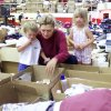 Tornado victims: Midwest City residents Jenny Parkerson and son Roy 2, and Janie 3, look through supplies in the temporary relief center at Del City HS Gym.