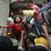 Photo - FILE – In this Thursday, April 25, 2013 file photo, a Bangladeshi woman survivor is lifted out of the rubble by rescuers at the site of the Rana Plaza garment factory building that collapsed Wednesday in Savar, near Dhaka, Bangladesh. A Bangladeshi garment industry leader on Saturday, April 18, 2015, guardedly welcomed Italian retailer Benetton's pledge of more than $1 million to victims of the factory collapse that killed over 1,100 people two years ago, saying it had come late but was appreciated. (AP Photo/Kevin Frayer, File)