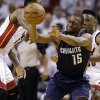 Photo - Charlotte Bobcats' Kemba Walker (15) passes the ball as Miami Heat's Norris Cole, right, and another player defend during the first half in Game 2 of an opening-round NBA basketball playoff series, Wednesday, April 23, 2014, in Miami. (AP Photo/Lynne Sladky)