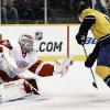 Detroit Red Wings goalie Jonas Gustavsson (50), of Sweden, gloves a shot in front of Nashville Predators center Craig Smith 1during the second period of an NHL hockey game Tuesday, Feb. 19, 2013, in Nashville, Tenn. (AP Photo/Mark Humphrey)