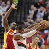 Photo - Houston Rockets' Terrence Jones, left, defends against Portland Trail Blazers' LaMarcus Aldridge, center, during the first half of an NBA basketball game in Portland, Ore., Thursday Dec. 12, 2013. (AP Photo/Greg Wahl-Stephens)