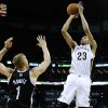 Photo - New Orleans Pelicans forward Anthony Davis (23) shoots the ball over Brooklyn Nets forward Mason Plumlee (1) during the second half of an NBA basketball game in New Orleans, Monday, March 24, 2014. The Pelicans won 109-104. (AP Photo/Jonathan Bachman)