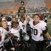 Wagoner\'s Kevin Peterson holds up the state championship trophy beside Heath Wilson, right, and Lawrence Evitt after beating Clinton 23-0 in the class 4A state championship high school football game at Boone Pickens Stadium in Stillwater, Okla., Friday, Dec. 2, 2011. Photo by Bryan Terry, The Oklahoman