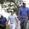 Tiger Woods, from right, Rory McIlroy, of Northern Ireland, and Adam Scott, of Australia, walk down from the fifth tee box during the first round of the U.S. Open golf tournament at Merion Golf Club, Thursday, June 13, 2013, in Ardmore, Pa. (AP Photo/Gene J. Puskar)