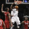 Photo - Brooklyn Nets forward Gerald Wallace (45) dunks between Miami Heat center Chris Bosh (1) and forward LeBron James (6) during the first half of an NBA basketball game Wednesday, Jan. 30, 2013, in New York. (AP Photo/Kathy Willens)