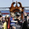 Johnny Sauter holds his son, Penn, as his wife, Cortney, left, joins him as he celebrates after winning the Kroger 250 NASCAR Truck series auto race at Martinsville Speedway in Martinsville, Va., Saturday, April 6, 2013. (AP Photo/Steve Helber)