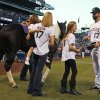 Photo - After being given a gelding paint horse named Tobiano as a retirement present, Colorado Rockies first baseman Todd Helton, right, joins his daughter Tierney Faith, second from right, and his wife Christy and daughter Gentry Grace in looking over the horse before the Rockies played the Boston Red Sox in a baseball game in Denver on Wednesday, Sept. 25, 2013. Helton, who will retire at season's end, was playing in his final home game for the Rockies. (AP Photo/David Zalubowski)