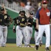 Washington Nationals manager Davey Johnson, right, walks off the field as Pittsburgh Pirates celebrate following a baseball game at Nationals Park, Wednesday, July 24, 2013, in Washington. Pittsburgh won 4-2. (AP Photo/Pablo Martinez Monsivais)
