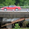 Flood debris is seen wedged underneath a bridge as a motorist passes on Park Avenue in Paducah, Ky., June 1, 2013. Severe weather overnight brought 6 to 8 inches of rain to the region. (AP Photo/Stephen Lance Dennee)