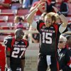 Texas Tech quarterback Taylor Potts (15) leaps in the air next to Edward Britton (27) as the song