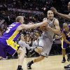 San Antonio Spurs\' Manu Ginobili, center, of Argentina, drives between Los Angeles Lakers\' Steve Blake, left, and Dwight Howard during the second half of Game 1 of their first-round NBA basketball playoff series, Sunday, April 21, 2013, in San Antonio. San Antonio won 91-79. (AP Photo/Eric Gay)