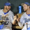 UCLA\'s Pat Gallagher (27) and Eric Filia (4) bump fists in the dugout after winning 4-1 against North Carolina in an NCAA College World Series baseball game in Omaha, Neb., Friday, June 21, 2013. (AP Photo/Francis Gardler)