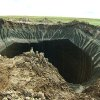Photo - This frame grab made Wednesday, July 16, 2014, shows a crater, discovered recently in the Yamal Peninsula, in Yamalo-Nenets Autonomous Okrug, Russia. Russian scientists said Thursday July 17, 2014 that they believe a 60-meter wide crater, discovered recently in far northern Siberia, could be the result of changing temperatures in the region. Andrei Plekhanov, a senior researcher at the Scientific Research Center of the Arctic, traveled on Wednesday to the crater. Plekhanov said 80 percent of the crater appeared to be made up of ice and that there were no traces of an explosion, eliminating the possibility that a meteorite had struck the region. (AP Photo/Associated Press Television)