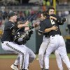 Photo - Vanderbilt players hug Tyler Campbell (2) after he hit a single in the 10th inning to score Rhett Wiseman for a 4-3 win over Texas in an NCAA baseball College World Series game in Omaha, Neb., Saturday, June 21, 2014. Vanderbilt advances to the championship series. (AP Photo/Ted Kirk)