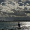 A jogger in Berkeley, Calif., runs beneath storm clouds on Monday, Nov. 9, 2015. A storm crossed the region Monday morning, bringing rain, thunder and lightning to the drought-parched region. (AP Photo/Noah Berger)