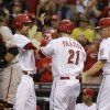 Photo - Cincinnati Reds' Todd Frazier (21) is congratulated by Joey Votto and Jay Bruce (32) after Frazier hit a three-run home run off San Francisco Giants starting pitcher Michael Kickham in the third inning of a baseball game, Monday, July 1, 2013, in Cincinnati. Catcher Buster Posey waits at left. (AP Photo/Al Behrman)