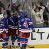 Photo - New York Rangers Derick Brassard, third from left, celebrates with teammates and fans after scoring a goal during the first period of an NHL hockey game against the Florida Panthers, Thursday, April 18, 2013 at Madison Square Garden in New York.  (AP Photo/Mary Altaffer)