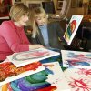 Photo - Sue Hale, left, who's paintings will be featured in a new exhibit to raise funds for EduCare, looks with Kelli Dupuy at some children's artwork at her studio in the Paseo district in Oklahoma City, OK, Monday, October 29, 2012,  By Paul Hellstern, The Oklahoman