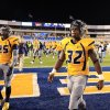 West Virginia\'s Ryan Clarke (32) and Darwin Cook (25) walk off the field after their NCAA college football game against TCU in Morgantown, W.Va., on Saturday, Nov. 3, 2012. TCU won 39-38 in overtime. (AP Photo/Christopher Jackson) ORG XMIT: WVCJ121