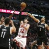 Chicago Bulls shooting guard Kirk Hinrich (12) shoots between Brooklyn Nets center Brook Lopez (11) and Deron Williams (8) during the second half of Game 3 of their first-round NBA basketball playoff series, Thursday, April 25, 2013, in Chicago. The Bulls won 79-76. (AP Photo/Charles Rex Arbogast)