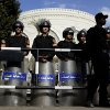 Egyptian riot policemen guard a gate of the presidential palace, background, amid ongoing protests, in Cairo, Egypt, Saturday, Dec. 8, 2012. Egypt\'s military has warned of \'disastrous consequences\' if the political crisis gripping the country is not resolved through dialogue.