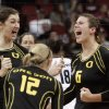 Oregon players Canace Finley, left, Katherine Fischer (12), and Liz Brenner (6) celebrate a second game victory over Penn State in the national semifinals of the NCAA college women\'s volleyball tournament semifinal in Louisville, Ky., Thursday, Dec. 13, 2012. (AP Photo/Garry Jones)
