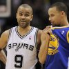 Photo - San Antonio Spurs guard Tony Parker, left, of France, talks to Golden State Warriors guard Stephen Curry during the first half of an NBA basketball game on Wednesday, April 2, 2014, in San Antonio. (AP Photo/Darren Abate)