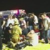 In this frame grab from video provided by Zach Reister, authenticated by checking against known locations and events, and consistent with Associated Press reporting, medical personnel attend the injured after a fireworks show in Simi Valley, Calif., Thursday, July 4, 2013. More than two dozen people were injured when a wood platform holding live fireworks tipped over, sending the pyrotechnics into the crowd at the Fourth of July show, authorities said Friday. (AP Photo/Zach Reister)