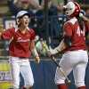 Oklahoma\'s Brianna Turang, left, celebrates with Lauren Chamberlain after scoring in the third inning against Washington during a Women\'s College World Series softball game at ASA Hall of Fame Stadium in Oklahoma City, Sunday, June, 2, 2013. Photo by Sarah Phipps, The Oklahoman Download