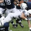 Photo - Penn State running back Deron Thompson (36) is tackled by Penn State cornerback Adrian Amos (4) and  linebacker Mike Hull (43) in the first half of their spring NCAA college football game on Saturday, April 20, 2013, in State College, Pa. (AP Photo/Keith Srakocic)