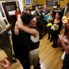 Thomas Carroll, 48, of Hoboken, N.J., center left, gives a kiss to his new bride, Stephanie McClure, of Smyrna, Ga., as a small party cheers for them moments after they were married by city clerk James Farina at Hoboken City Hall, Tuesday, Nov. 6, 2012, in Hoboken, N.J. The couple was scheduled to get married on Nov. 3, in Point Pleasant, N.J., but Superstorm Sandy washed away their wedding. Meanwhile, residents of Hoboken voted in the presidential election on Election Day in a polling place located in the adjacent room. (AP Photo/Julio Cortez) ORG XMIT: NJJC127