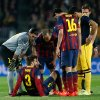 Photo - Players check on Barcelona's Gerard Pique, on the ground, after he injured himself during a first leg quarterfinal Champions League soccer match between Barcelona and Atletico Madrid at the Camp Nou stadium in Barcelona, Spain, Tuesday April 1, 2014. Pique had to be substituted. (AP Photo/Emilio Morenatti)