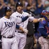 Photo - Tampa Bay Rays' James Loney, left, and Matt Joyce, center, head to the dugout past Texas Rangers catcher Robinson Chririnos, right, after Joyce's two-run home run during the fourth inning of a baseball game on Saturday, April 5, 2014, in St. Petersburg, Fla. (AP Photo/Steve Nesius)