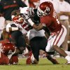 Oklahoma\'s Demontre Hurst (6) and Tony Jefferson (1) bring down Texas Tech\'s Eric Ward (18) during the college football game between the University of Oklahoma Sooners (OU) and the Texas Tech University Red Raiders (TTU) at Gaylord Family-Oklahoma Memorial Stadium in Norman, Okla., Saturday, Oct. 22, 2011. Photo by Bryan Terry, The Oklahoman