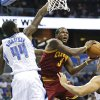 Photo - Cleveland Cavaliers' Dion Waiters (3) tries to shoot between Orlando Magic's Andrew Nicholson (44) and Tobias Harris, right, during the first half of an NBA preseason basketball game in Orlando, Fla., Friday, Oct. 11, 2013. (AP Photo/John Raoux)