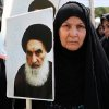 Photo - FILE - In this June 20, 2014 file photo, an Iraqi woman living in Iran holds a poster of the Grand Ayatollah Ali al-Sistani, Iraq's top Shiite cleric, in a demonstration against Sunni militants of the al-Qaida-inspired Islamic State of Iraq and the Levant, or ISIL, and to support Ayatollah al-Sistani, in Tehran, Iran. Prominent Shiite leaders pushed Thursday, June 26, 2014, for the removal of Iraqi Prime Minister Nouri al-Maliki as parliament prepared to start work next week on putting together a new government, under intense U.S. pressure to rapidly form a united front against an unrelenting Sunni insurgent onslaught. (AP Photo/Ebrahim Noroozi, File)