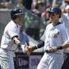 New York Yankees\' Kelly Johnson, right, celebrates with Jacoby Ellsbury after scoring during the fifth inning of a baseball game against the Cincinnati Reds at Yankee Stadium on Sunday, July 20, 2014, in New York. (AP Photo/Seth Wenig)