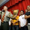 Sharing the stage with David Olivas (right) and the rest of the boys soccer team, Principal Chris Brewster leads a
