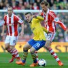 Photo - Arsenal's Jack Wilshere, centre, shields the bal from Stoke's Peter Crouch during the English Premier League soccer match between Stoke City and Arsenal at Britannia Stadium in Stoke On Trent, England, Saturday, March 1, 2014. (AP Photo/Rui Vieira)