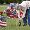 A woman puts material inside a vase before placing flowers in it. Individuals and families visited cemeteries across the state in observance of Memorial Day. Most brought floral decorations. Some brought American flags and others placed crosses at gravesites. But all were there to remember loved ones who have died. At Arlington Memory Gardens, 3400 N. Midwest Blvd., in Midwest City, about 100 people gathered for the cemetery\'s 54th annual Memorial Day observance, a ceremony marked by the dropping of red poppies beside white crosses, the playing of taps and a rifle volley by a group of veterans. The ceremony is organized by the Clarence L. Tinker American Legion Post 170. Rick Doty, commander of Post 170, said local Boy Scouts and Girl Scouts placed 2500 American flags on graves on Saturday. May 25, 2013. Maj. Gen. Myles Deering delivered the address. Deering is Oklahoma\'s Adjutant General. Photo by Jim Beckel, The Oklahoman.