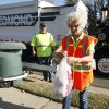 Photo - Edmond sanitation truck driver Jeff Whitfield watches former Mayor Saundra Naifeh, president of Edmond Beautiful, tie a bag of trash. PHOTO BY PAUL HELLSTERN, THE OKLAHOMAN. <strong>PAUL HELLSTERN - Oklahoman</strong>