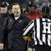 Photo -   Cincinnati coach Butch Jones, left, questions a penalty call by head linesman Steve Matarante, right, in the second half of the NCAA college football game against Louisville, in Louisville, Ky., Friday, Oct. 26, 2012. (AP Photo/Garry Jones)