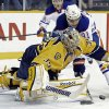 Nashville Predators goalie Pekka Rinne (35), of Finland, dives on the puck as Edmonton Oilers left wing Magnus Paajarvi (91), of Sweden, reaches for it in the first period of an NHL hockey game on Monday, March 25, 2013, in Nashville, Tenn. (AP Photo/Mark Humphrey)