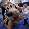 Photo -   Two-year-old Adisen Lee, from New York, meets Disney character Pluto in New York's Times Square, Wednesday, Oct. 17, 2012. On Wednesday, Disney announced a new program for 2013,