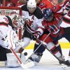 Photo - New Jersey Devils goalie Cory Schneider, left, and defenseman Andy Greene, second from left, defend against Washington Capitals right wing Joel Ward (42) during the second period of an NHL hockey game on Saturday, Feb. 8, 2014, in Washington. (AP Photo/ Evan Vucci)