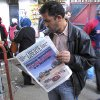 A man reads a newspaper headlining