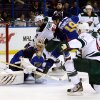 Photo - St. Louis Blues goalie Jaroslav Halak, of the Czech Republic, is unable to block a shot by Minnesota Wild's Jared Spurgeon, right, during the first period of a preseason NHL hockey game Friday, Sept. 27, 2013, in St. Louis. (AP Photo/Scott Kane)