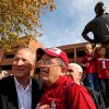 Photo - Barry Switzer poses for photos with fans as his grandchildren play on a statue of the former coach before the college football game between the Texas A&M Aggies and the University of Oklahoma Sooners (OU) at Gaylord Family-Oklahoma Memorial Stadium on Saturday, Nov. 5, 2011, in Norman, Okla. Photo by Bryan Terry, The Oklahoman