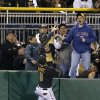 Photo - Pittsburgh Pirates left fielder Starling Marte (6) climbs the wall chasing the ball as fans reach for the home run ball hit by Toronto Blue Jays' Colby Rasmus in the fourth inning of a baseball game on Friday, May 2, 2014, in Pittsburgh. (AP Photo/Keith Srakocic)