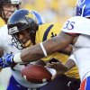 West Virginia quarterback Geno Smith (12) is sacked by Kansas\' Toben Opurum (35) and John Williams (71) during the second quarter of their NCAA college football game in Morgantown, W.Va., on Saturday, Dec. 1, 2012. (AP Photo/Christopher Jackson)